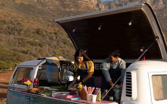 Side view of a young mixed race couple busy preparing food standing in an open top van offering a range of takeaway food for sale — Stock Photo