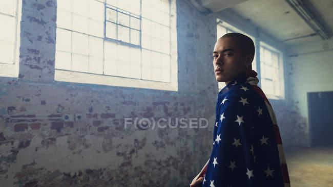 Seitenansicht eines jungen hispanisch-amerikanischen Mannes mit einer amerikanischen Flagge über den Schultern, der aufmerksam in die Kamera blickt, während er in einer leeren Lagerhalle steht — Stockfoto