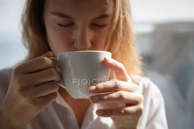Вид спереди на молодую белую женщину в белой рубашке, пьющую кофе с закрытыми глазами . — стоковое фото