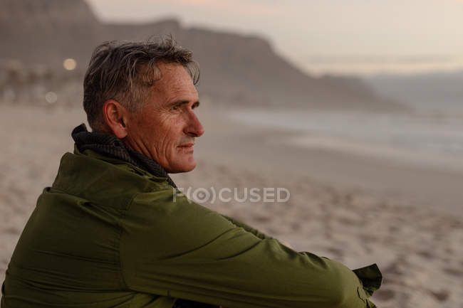 Side view close up of a mature Caucasian man enjoying the view sitting on a beach beside the sea at sunset — Stock Photo