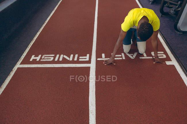 Vue en angle élevé de l'athlète masculin afro-américain handicapé au point de départ sur la piste de course dans le centre de remise en forme — Photo de stock