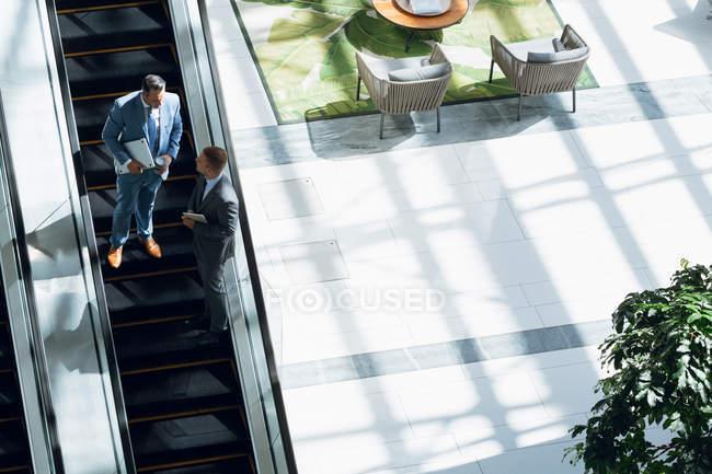 Vista ad alto angolo di uomini d'affari che interagiscono tra loro mentre si spostano al piano di sotto sulla scala mobile in ufficio . — Foto stock