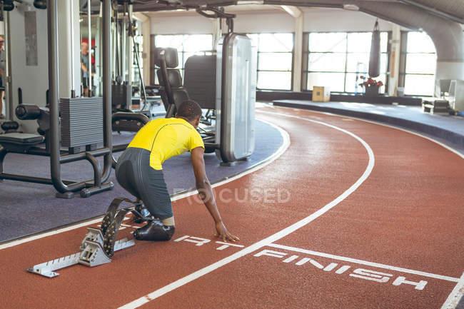 Вид сзади афроамериканского спортсмена-инвалида на стартовом блоке на беговой дорожке в фитнес-центре — стоковое фото