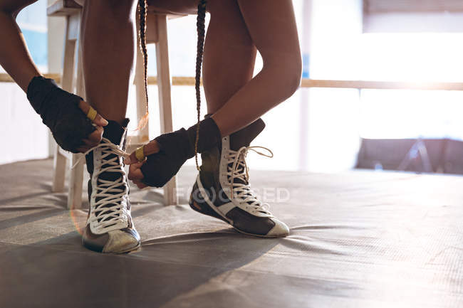Close-up of female boxer tying shoelaces in boxing ring at fitness center. Strong female fighter in boxing gym training hard. — Stock Photo