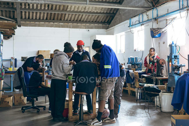 Rear view of a diverse group of male workers gathered around a table in discussion in a workshop at a cricket ball factory, while colleagues work at machines in the background. — Stock Photo