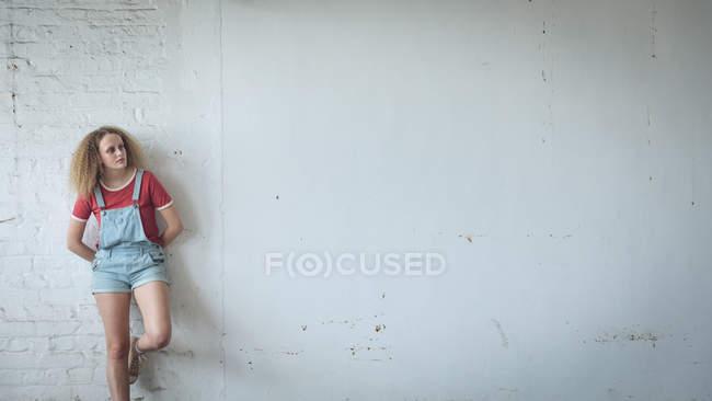 Vista frontal de una joven mujer caucásica con el pelo rizado de pie contra una pared blanca - foto de stock