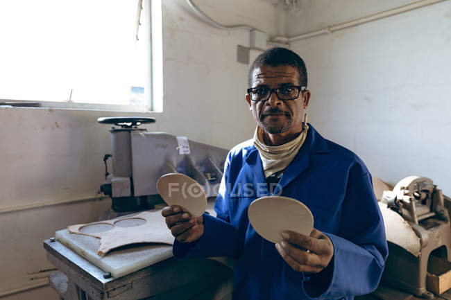 Portrait of a middle aged African American man wearing glasses working at a factory making cricket balls, looking to camera and holding leather cut out shapes. — Stock Photo