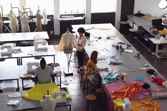 Blick aus der Vogelperspektive auf eine vielfältige Gruppe von Modestudenten, die in einem Atelier der Modehochschule an Entwürfen arbeiten — Stockfoto