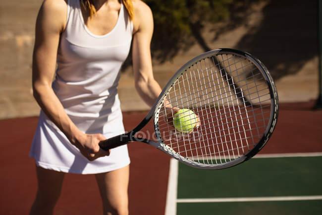 Вид спереди на женщину, играющую в теннис в солнечный день, готовящуюся к подаче — стоковое фото
