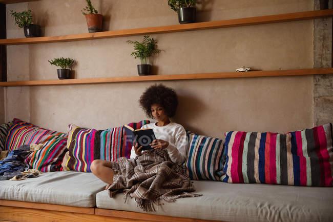 Vue de face d'une jeune femme métisse assise sur un canapé lisant un livre à la maison, appuyée sur des coussins avec une couverture sur les jambes — Photo de stock