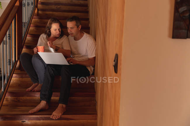 Front view of a middle aged Caucasian man and woman sitting on a staircase in their home and using a computer laptop — Stock Photo