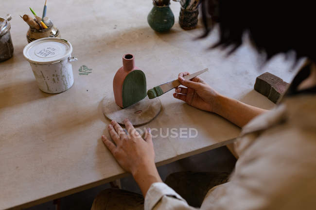 Over the shoulder view of a female potter sitting at a work table painting a colored glaze on a clay flask in a pottery studio — Stock Photo