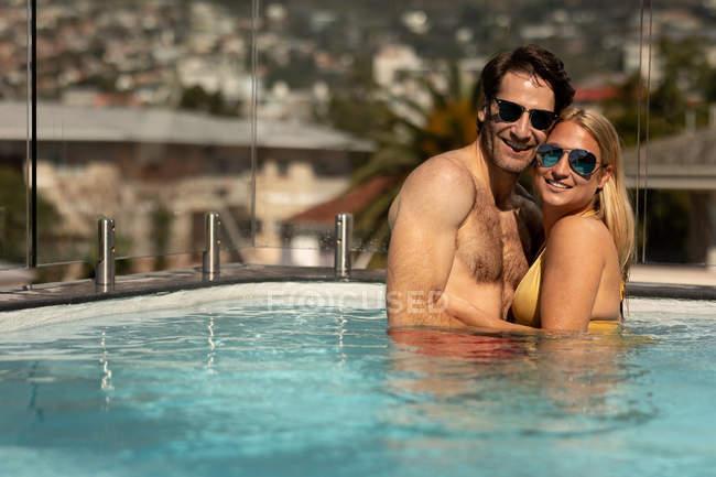 Портрет щасливого молодого Кавказького подружжя, що розслабляє на відпочинку в басейні, Усміхаючись до камери — стокове фото