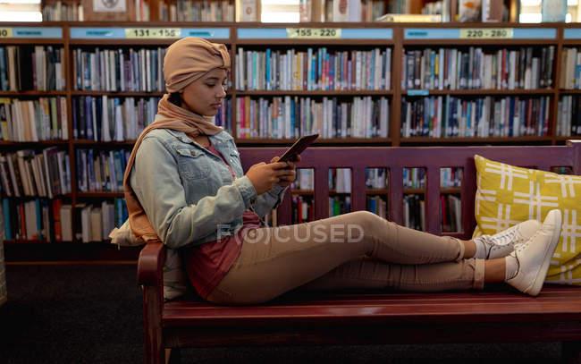 Бічний вид на молоду азіатську студентку, яка носить хіджаб за допомогою планшетного комп