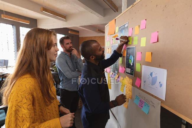 Бічний вид на молоду кавказьку жінку і чоловіка, що стоять і спостерігають за тим, як їхні молоді афроамериканські колеги пишуть на дошці ідей під час командного штурму під час творчого кабінету. — стокове фото