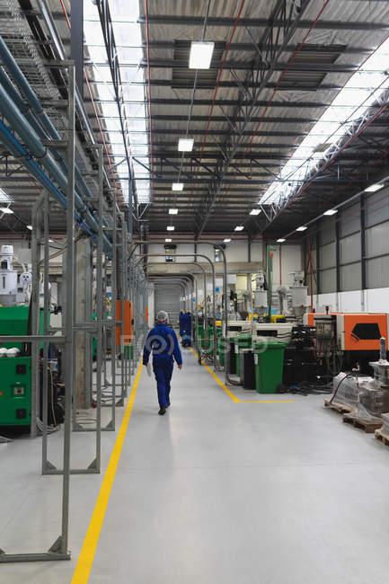 Вид сзади на работника завода в комбинезоне и сетке для волос, идущего мимо машин и оборудования на складе на заводе, с другими работниками на заднем плане — стоковое фото