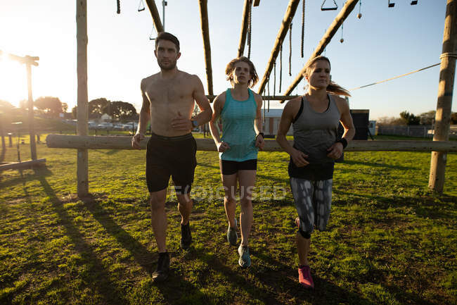 Вид спереди на двух молодых кавказских женщин и молодого кавказца, бегущего в открытом спортзале во время тренировочного лагеря — стоковое фото