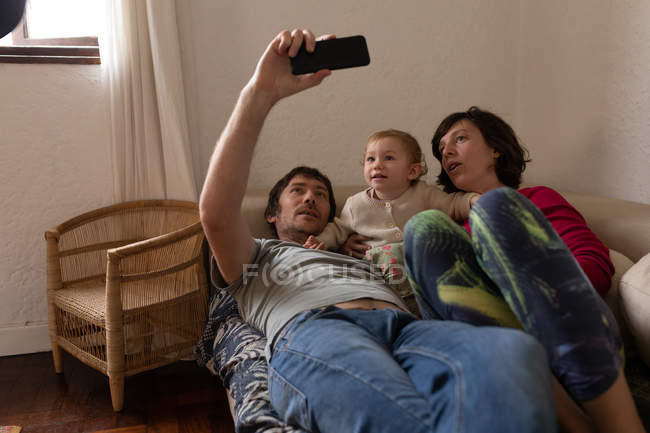 Front view of a young Caucasian father and mother lying on a sofa with their baby and taking a selfie — Stock Photo
