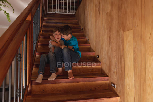 Portrait of two pre teen Caucasian boys sitting on a staircase at home, embracing and looking to camera — Stock Photo