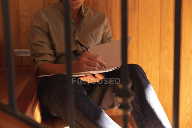 Передня частина людини сидить на сходах і робить нотатки. — стокове фото