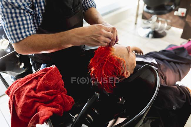 Зворотний вид на чоловічу перукарню та молоду кавказьку жінку з яскраво-червоним волоссям, пофарбованим у шерстяний салон. — стокове фото