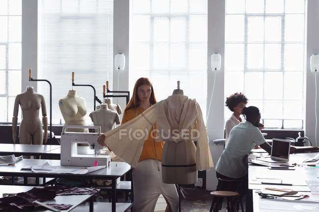 Front view of a young Caucasian female fashion students working on a garment on a mannequin in a studio at fashion college, with other students working in the background — Stock Photo
