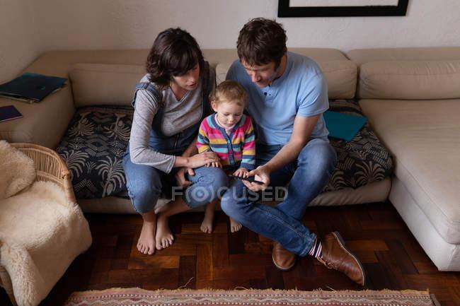 Вид спереди на молодого кавказского отца и мать, сидящих на диване и использующих смартфон со своим ребенком — стоковое фото