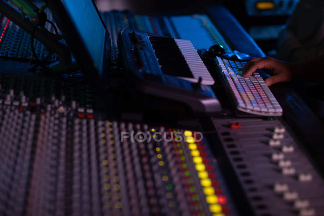 The hand of male sound engineer using a computer keyboard at a mixing desk in a recording studio — Stock Photo
