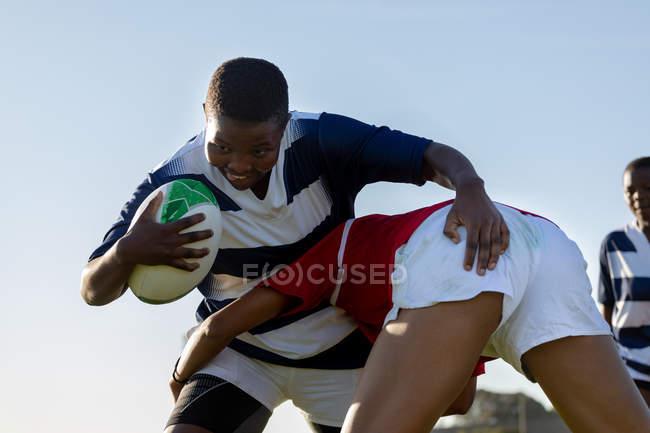 Vista frontale da vicino di due giovani giocatrici di rugby miste durante una partita, una giocatrice che corre con la palla e l'altra che la affronta, con un altro giocatore sullo sfondo — Foto stock