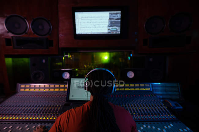 Задний план молодого инженера смешанной расы, сидящего и работающего за столом для микширования в студии звукозаписи в наушниках — стоковое фото