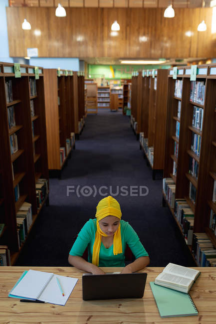 Front view of a young Asian female student wearing a hijab using a laptop computer and studying in a library — Stock Photo