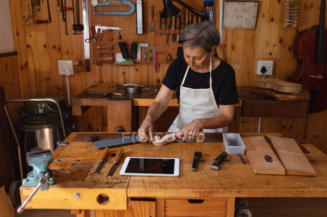 Front view close up of a senior Caucasian female luthier working on the scroll of a violin on a workbench in her workshop, with a tablet computer in front of her and tools hanging up on the wall in the background — Stock Photo