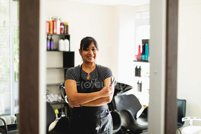 Portrait of a middle aged mixed race female hairdresser smiling to camera with her arms crossed in a hair salon — стокове фото
