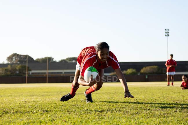 Vista frontal de una joven jugadora de rugby femenina adulta de raza mixta sosteniendo el balón y cayendo con él, buscando la línea durante un partido de rugby, con compañeros de equipo en segundo plano. - foto de stock