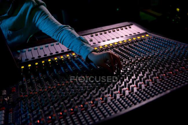 Средний вид мужчины-звукоинженера, идущего через микшерный стол в студии звукозаписи для настройки настроек канала — стоковое фото