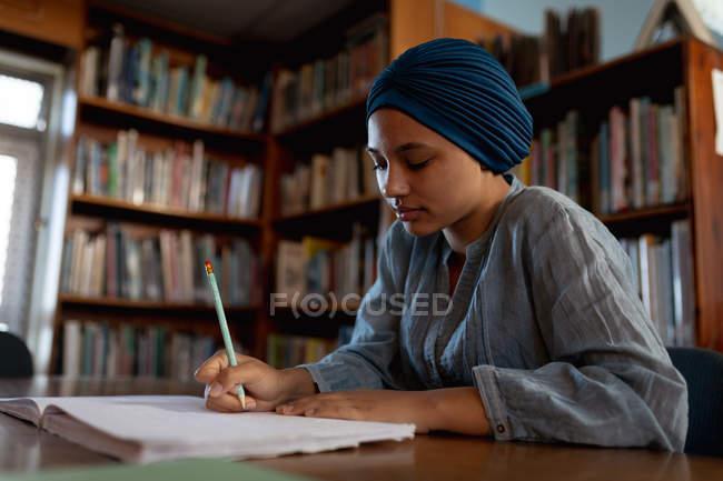 Vista laterale da vicino di una giovane studentessa asiatica con indosso un turbante che scrive e studia in una biblioteca — Foto stock