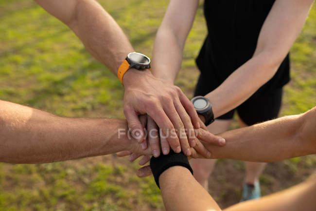 Высокоугловая низкая секция из трех взрослых, стоящих вместе и сложенных рук в единстве в открытом тренажерном зале во время тренировочного лагеря — стоковое фото