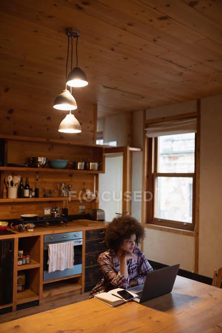 Vista elevata di una giovane donna da corsa mista che utilizza un computer portatile seduto al suo tavolo da cucina a casa, il suo smartphone e un libro accanto a lei — Foto stock