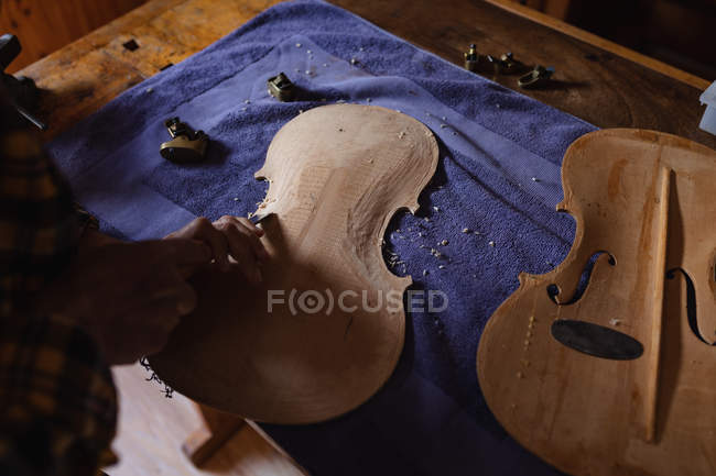 Close up of female luthier working on the body of a violin on a workbench in her workshop — Stock Photo