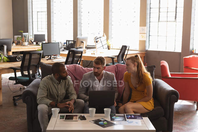 Front view of a young African American man and a young Caucasian woman and man sitting on a sofa in a creative office discussing a project and using a laptop computer — Stock Photo