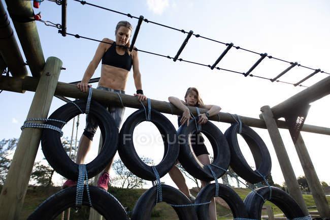 Vue avant de deux jeunes femmes caucasiennes grimpant au-dessus d'un mur de pneus sur un cadre d'escalade à une gymnastique extérieure pendant une session d'entraînement de bootcamp — Photo de stock