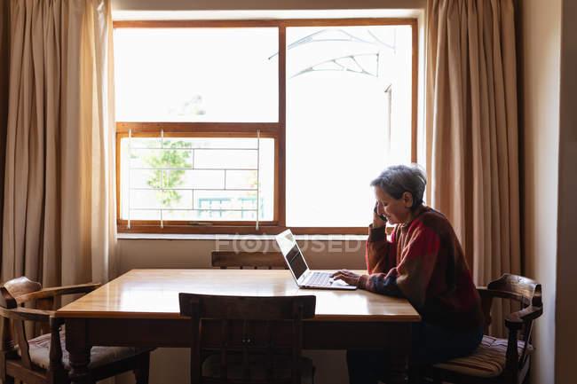 Vista laterale di una donna caucasica anziana seduta a un tavolo a casa facendo una telefonata e un computer portatile — Foto stock