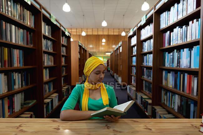 Vista frontal close up de uma jovem estudante asiática vestindo um hijab lendo um livro e estudando em uma biblioteca — Fotografia de Stock