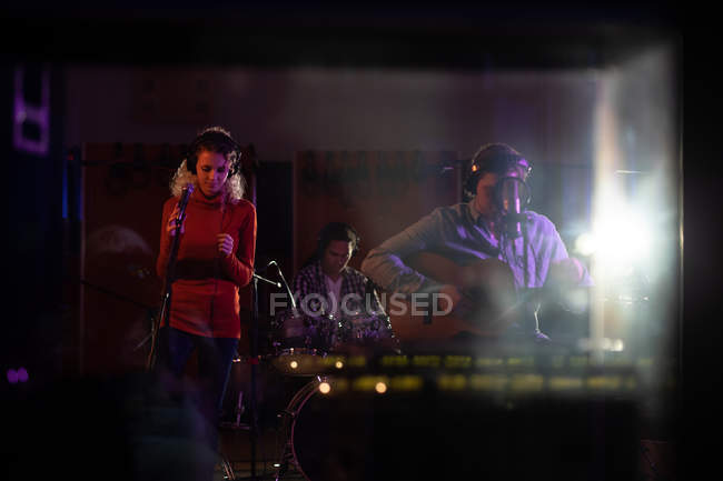 Front view of a young Caucasian female singer and a young Caucasian male singer guitarist performing during a session at a recording studio — Stock Photo