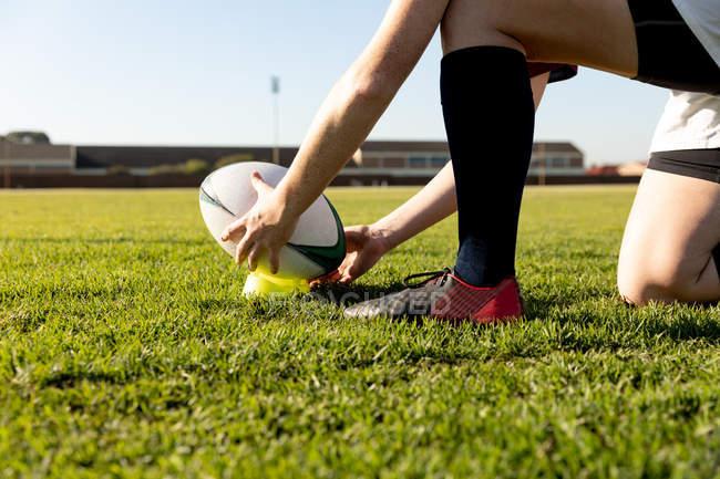 Vista laterale bassa sezione di giocatore di rugby femminile inginocchiato su un campo da rugby e impostare la palla su una tee per un calcio di posizione — Foto stock