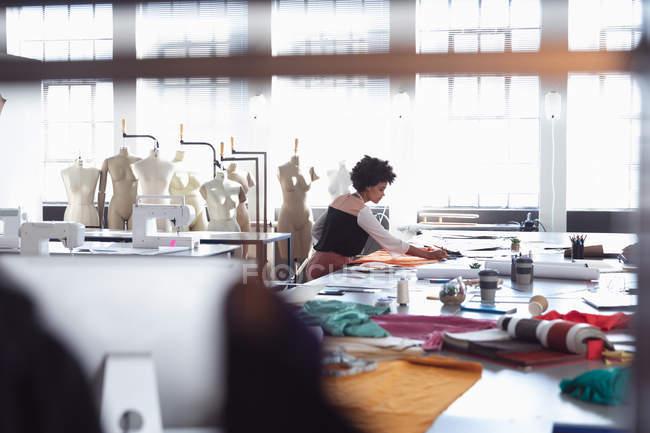 Vista lateral de una joven estudiante de moda de raza mixta sentada en una mesa trabajando en un diseño en un estudio de la universidad de moda, con maniquíes en el fondo - foto de stock
