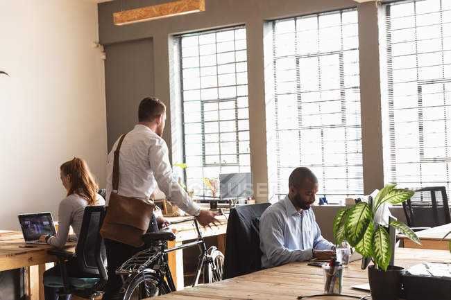 Rear view of a young Caucasian man wheeling a bicycle into a creative office, with a male and a female colleague sitting at desks working in the background — Stock Photo