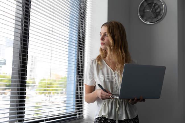 Вид спереди на молодую кавказку, стоящую с ноутбуком в руках и повернутую головой, выглядывающую из окна с жалюзи в современном офисе креативного бизнеса — стоковое фото