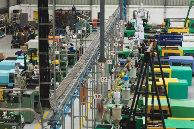 Высокий угол обзора рабочих завода, эксплуатирующих машины на складе на заводе по переработке — стоковое фото
