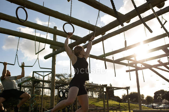 Side view of a young Caucasian woman hanging from rings on a climbing frame at an outdoor gym during a bootcamp training session, with a man climbing in the background — Stock Photo